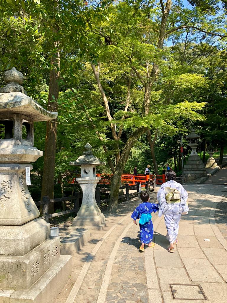 Mother and child in yukata walking to a temple.