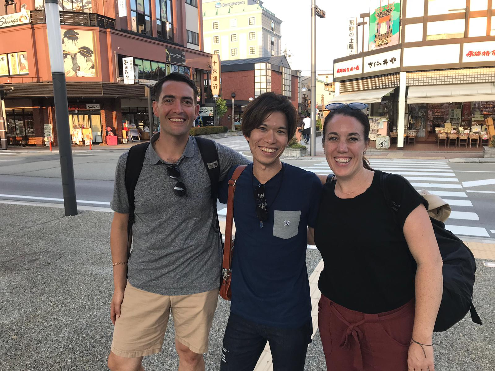 Three friends together on a street in Japan.