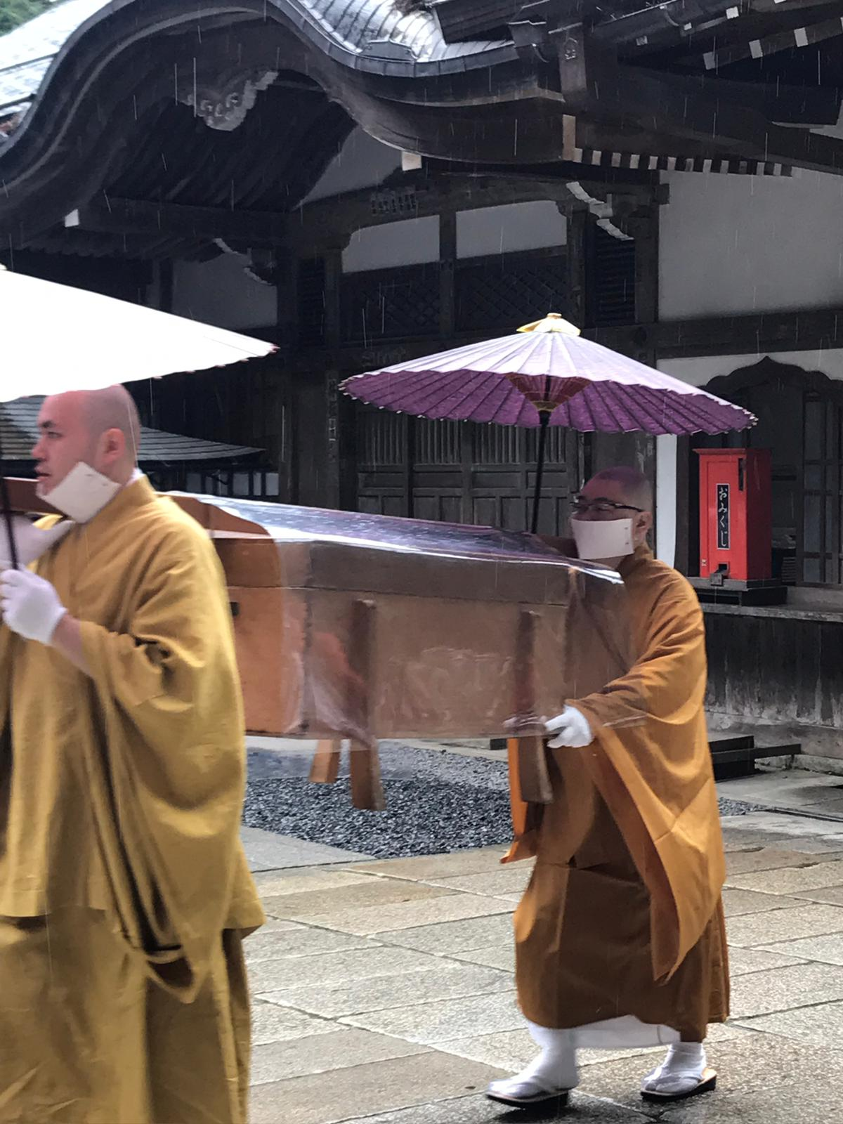 Monks carrying a box