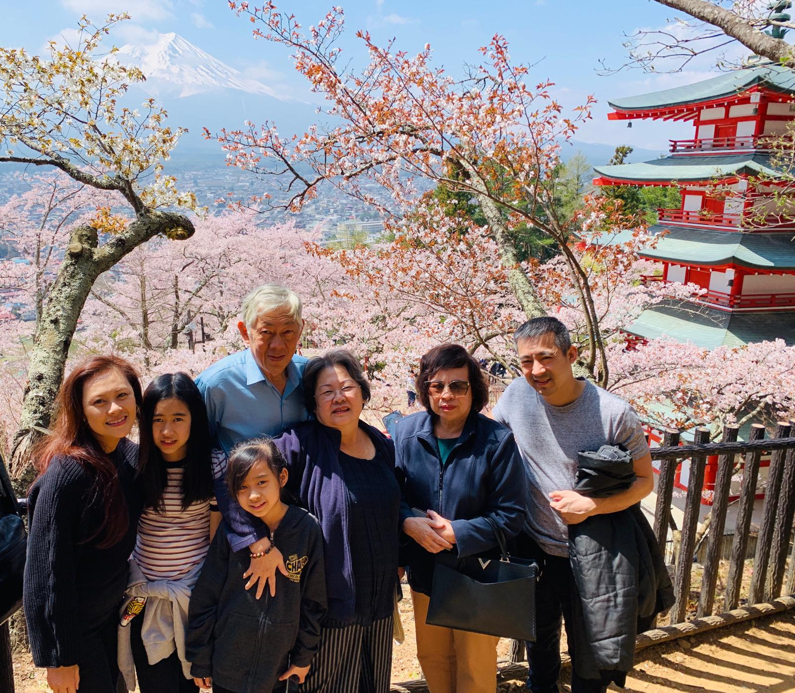 Family posing infront of pagoda and cherry blossoms