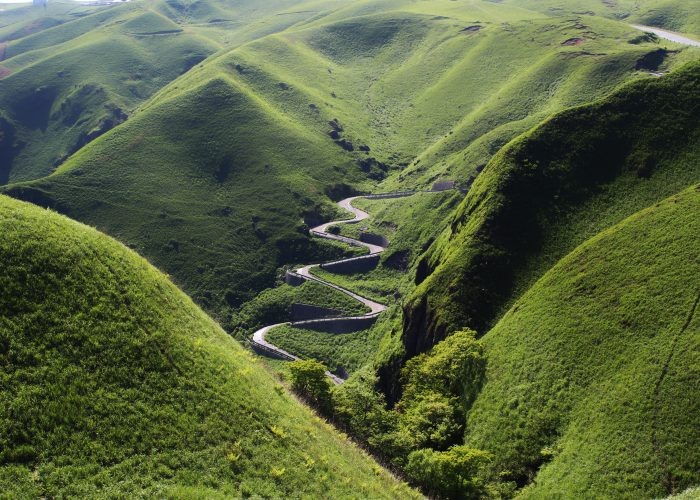 A zigzagging road surrounded by green mountains.