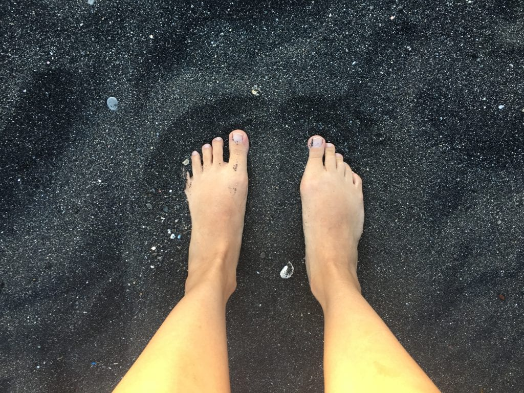 Two feet in black sand on Hachijojima